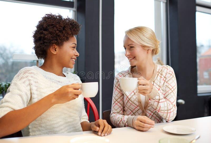 喝茶或咖啡的愉快的少妇在咖啡馆 库存图片