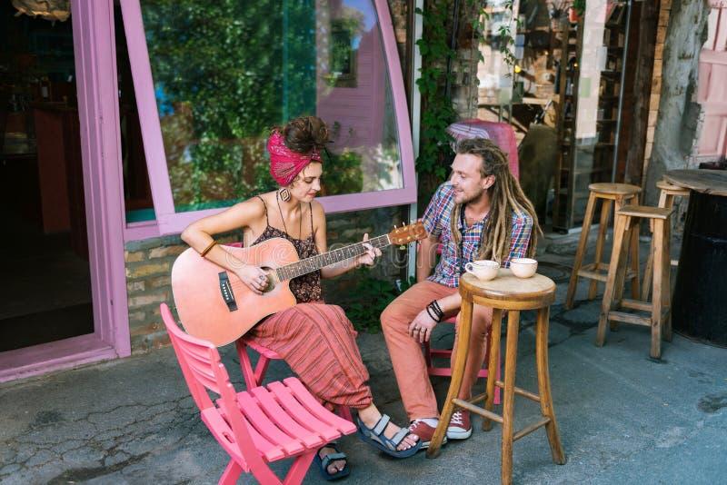 喝茶的创造性的嬉皮夫妇坐夏天大阳台 免版税库存图片