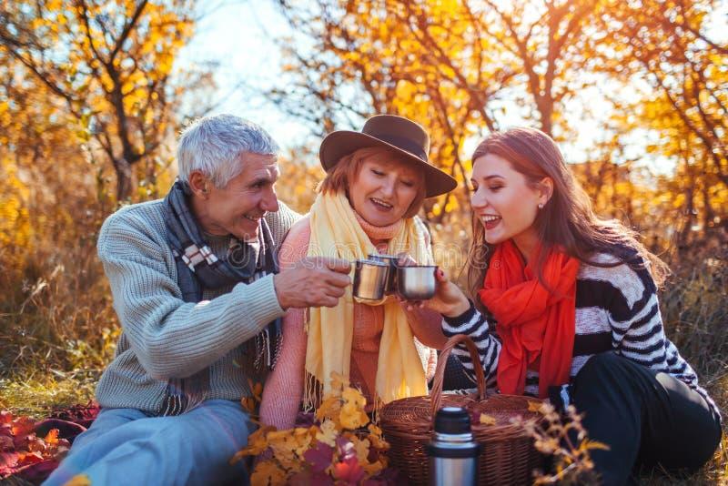 喝茶的资深父母在有他们的女儿的秋天森林里 家庭价值观 有野餐 免版税库存照片