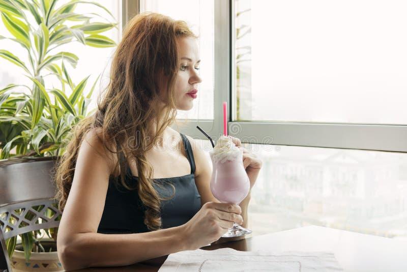 喝草莓调味的奶昔的年轻美女在窗口背景的一家餐馆在白天 ?treadled 免版税库存照片