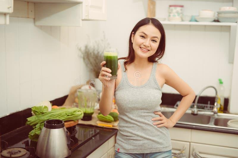 喝菜圆滑的人的俏丽的年轻女人在她的厨房里 免版税库存图片