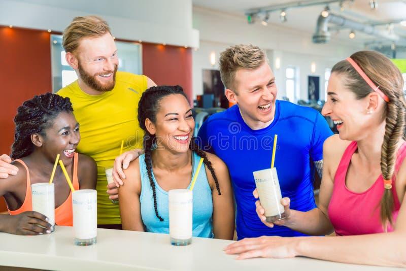 喝蛋白质的不同种族的小组快乐的朋友震动 图库摄影