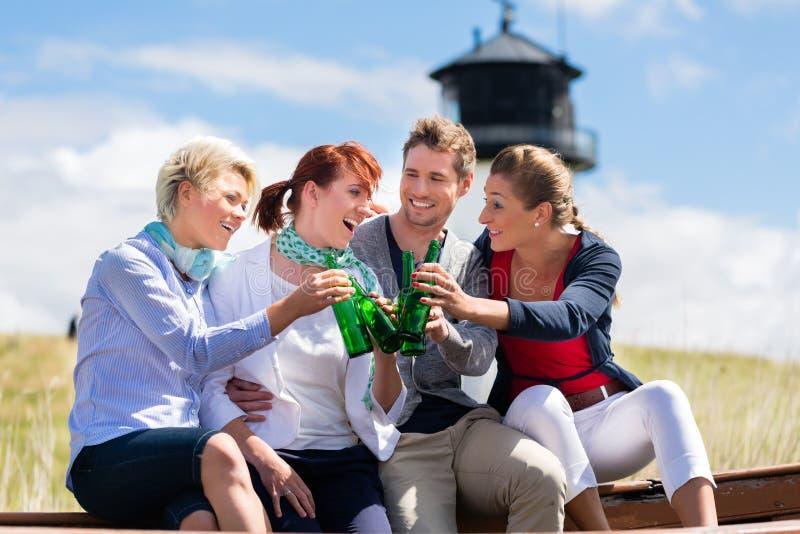 喝被装瓶的啤酒的朋友在海滩 免版税库存照片