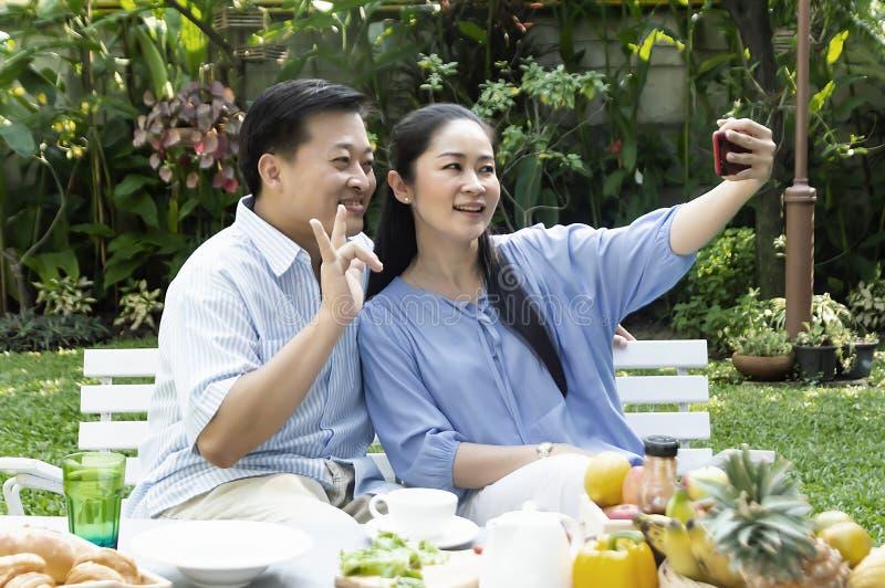 喝资深夫妇的下午茶和拍一张照片在庭院里 库存图片