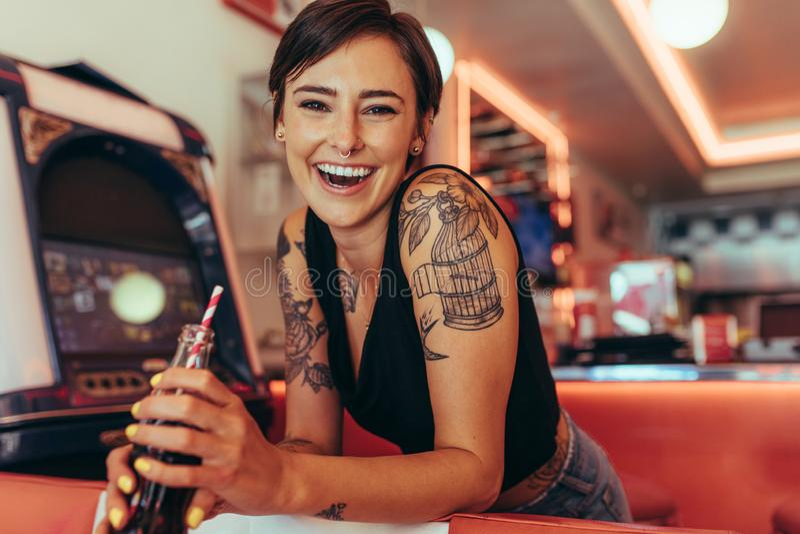 喝软饮料的吃饭的客人的微笑的妇女 免版税库存照片