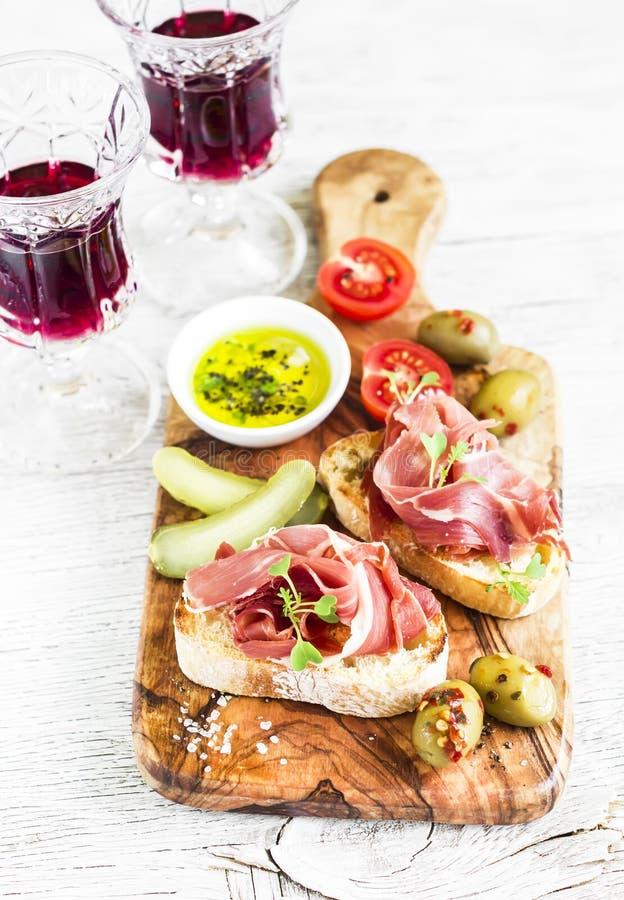 喝酒的可口开胃菜-敬酒用火腿,橄榄,蕃茄 免版税图库摄影
