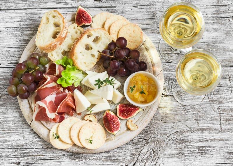 喝酒的可口开胃菜-火腿,乳酪,葡萄,薄脆饼干,无花果,坚果,果酱,在一个轻的木板和两块玻璃服务与 免版税库存图片