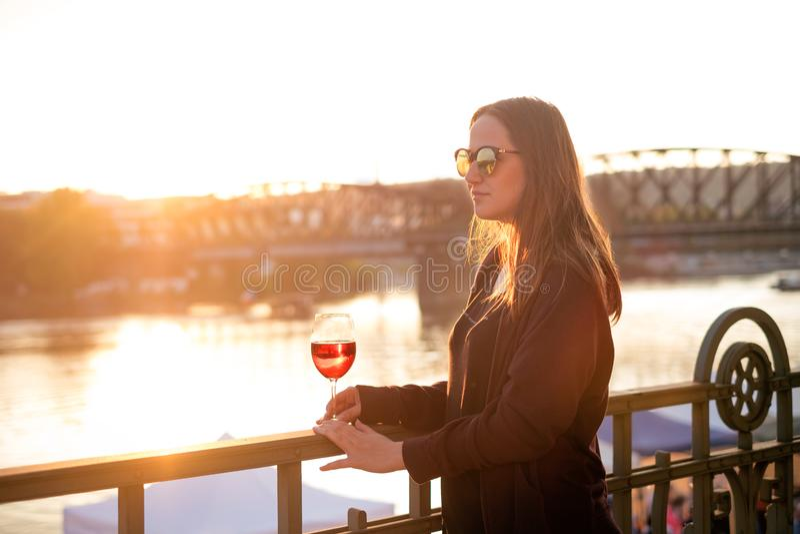 喝酒的妇女在城市在日落期间 玻璃红葡萄酒 业余时间的概念在城市和饮用的酒精的 免版税库存图片