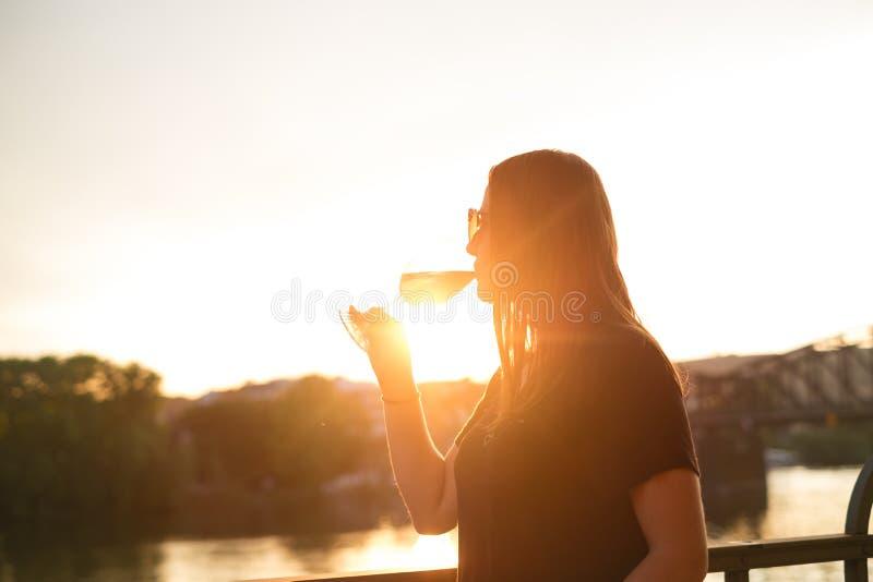 喝酒的妇女在城市在日落期间 玻璃红葡萄酒 业余时间的概念在城市和饮用的酒精的 库存照片