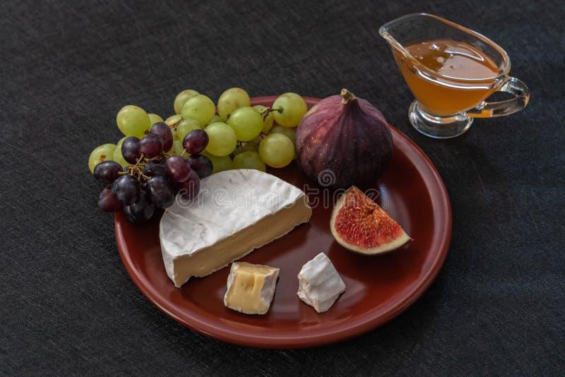 喝酒的点心开胃菜-无花果,咸味干乳酪乳酪,葡萄,蜂蜜在黑背景的一块陶瓷板材服务 免版税图库摄影