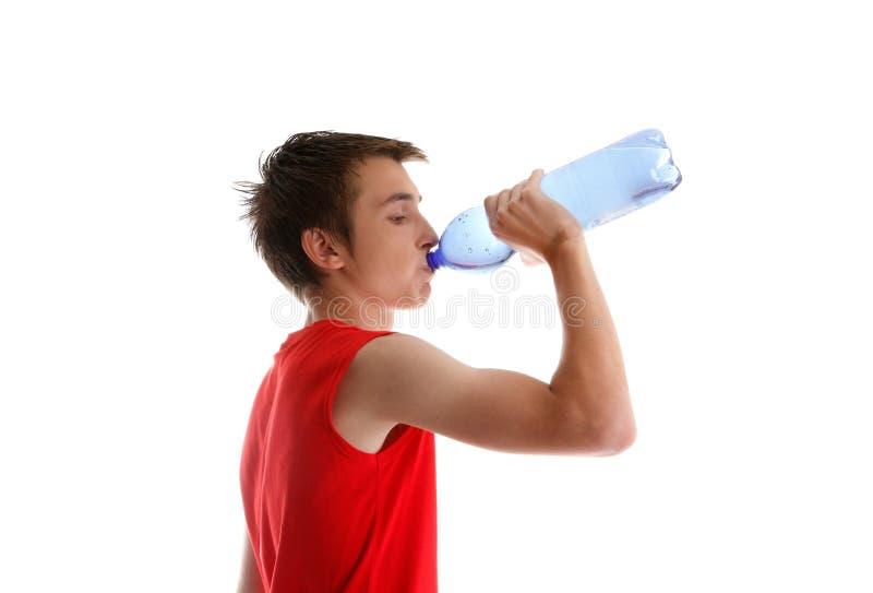 喝青少年的水的被装瓶的男孩 免版税图库摄影