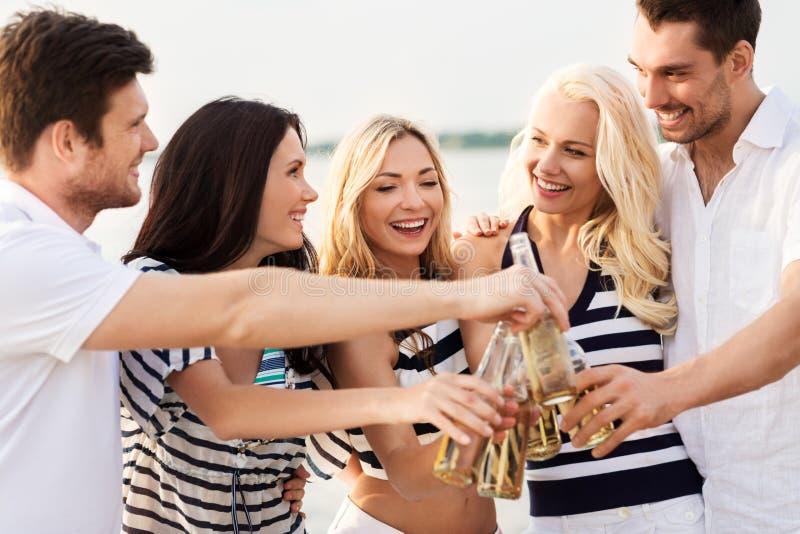喝非在海滩的愉快的朋友酒精啤酒 免版税库存照片