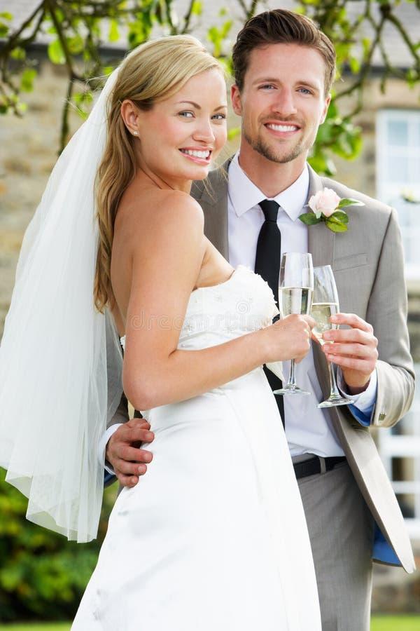 喝香宾的新娘和新郎在婚礼 免版税库存图片