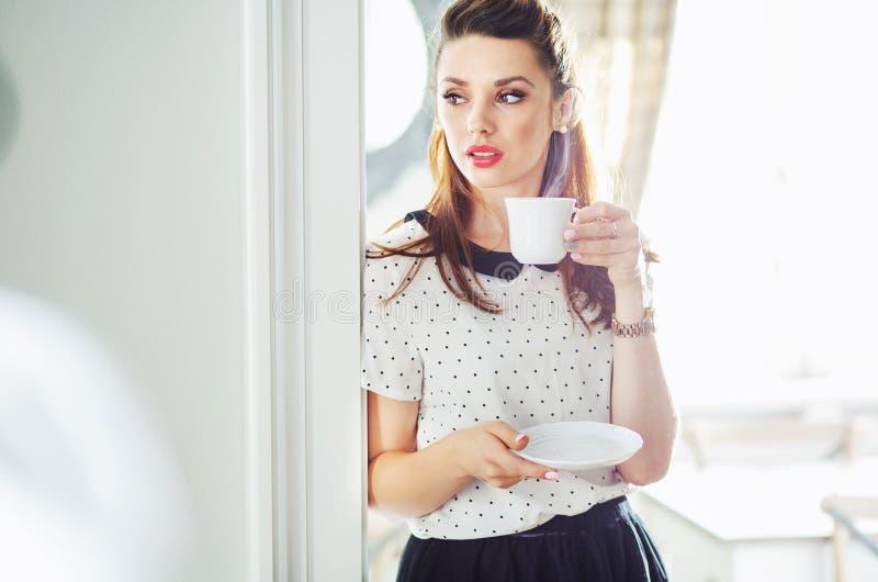 喝鲜美咖啡的可爱的妇女 免版税图库摄影