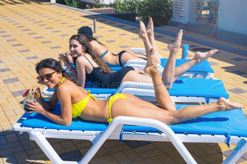 喝鸡尾酒的三个美丽的女孩在水池附近 免版税库存图片