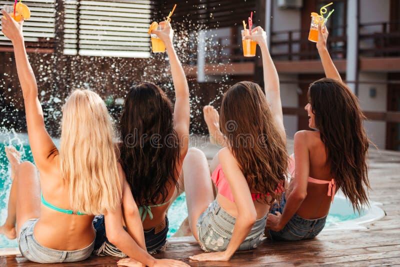 喝鸡尾酒的后面观点的四个快乐的女孩在水池 库存图片