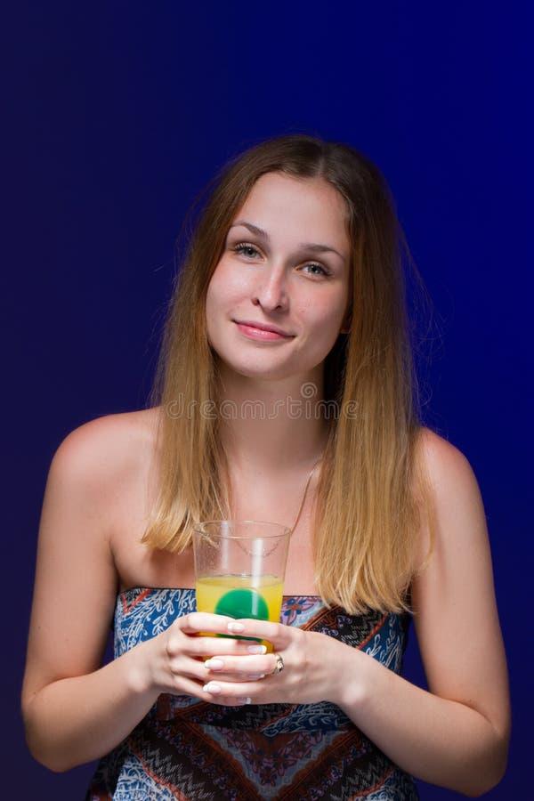 喝鸡尾酒的女孩反对蓝色背景 库存图片
