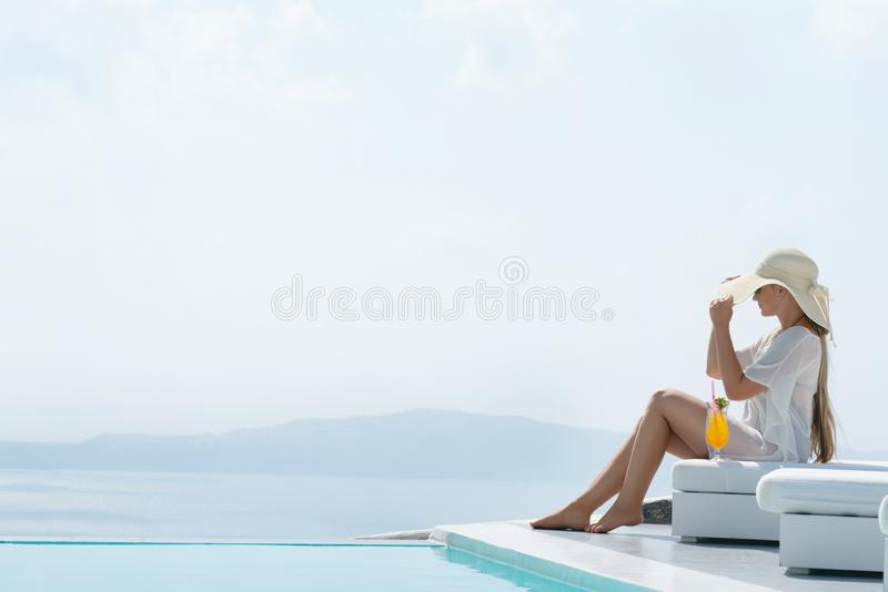 喝鸡尾酒的年轻女人享受圣托里尼一个宏伟的视图在水池附近 免版税库存图片
