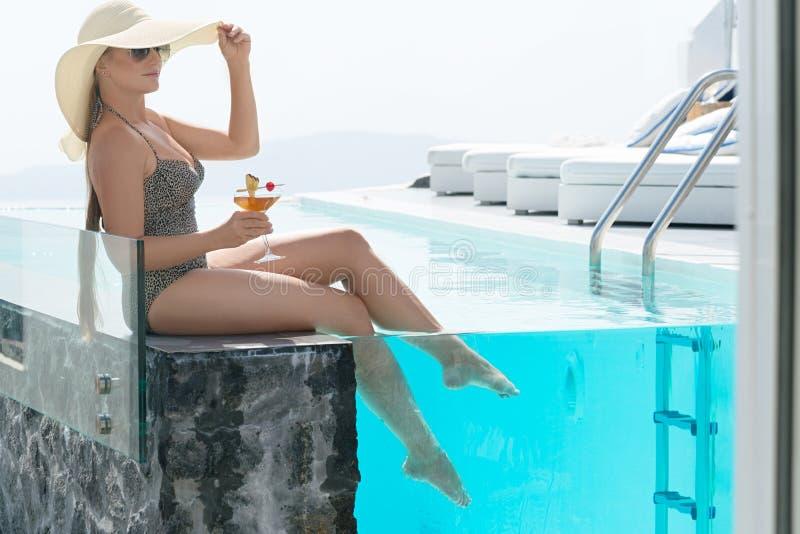 喝鸡尾酒的年轻女人享受圣托里尼一个宏伟的视图在水池附近 库存照片