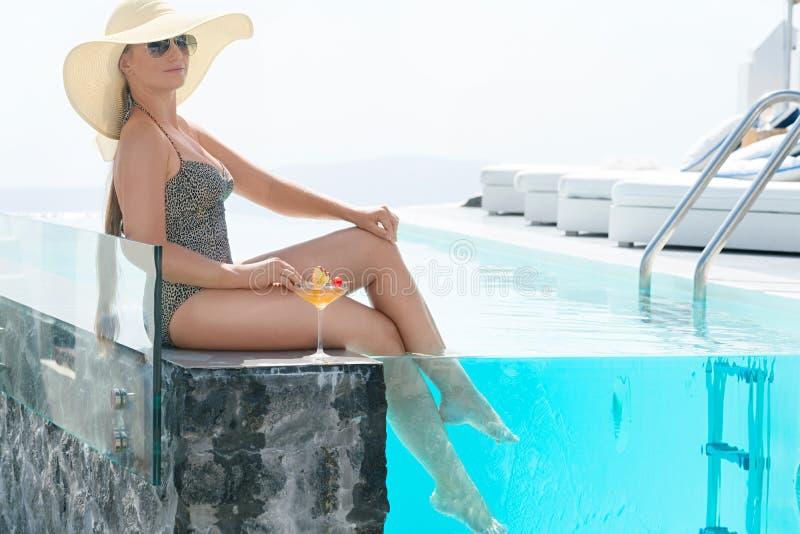 喝鸡尾酒的年轻女人享受圣托里尼一个宏伟的视图在水池附近 库存图片
