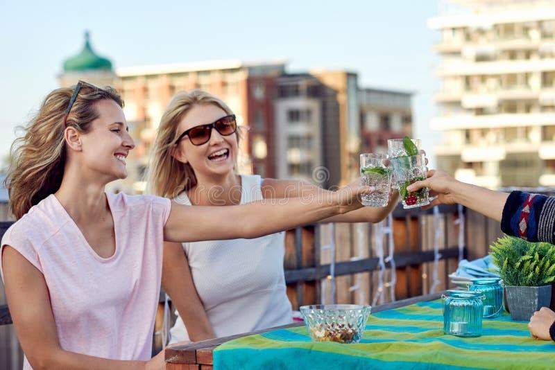 喝鸡尾酒的快乐的朋友 免版税库存图片