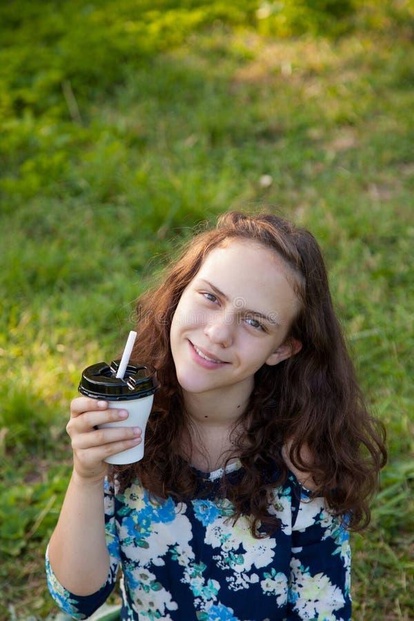 喝鸡尾酒的美丽的青少年女孩在一顿野餐在森林在夏天 库存图片