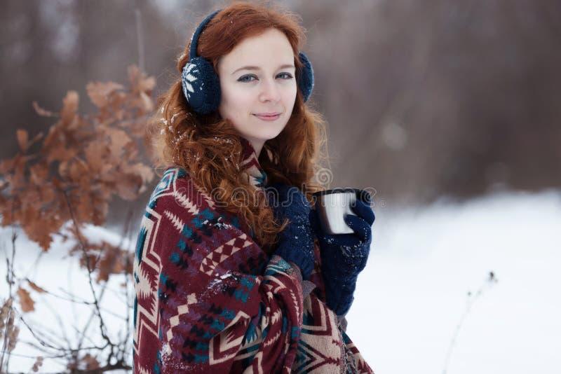 喝从一个杯子的可爱的年轻红发妇女一份热的饮料在冬天公园 免版税库存图片