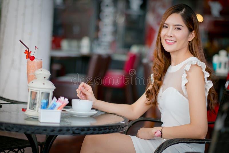 喝从一个杯子的妇女一份咖啡在餐馆大阳台 免版税库存照片
