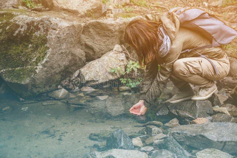 喝从小河的远足者妇女水 免版税库存图片