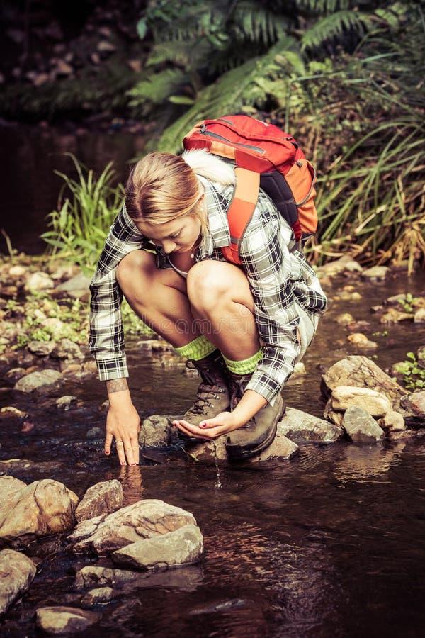 喝从小河的远足者 库存图片