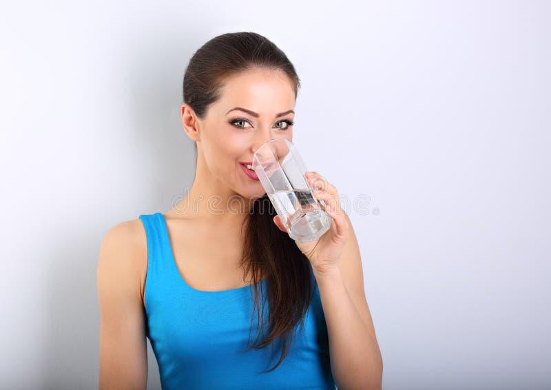 喝从玻璃的年轻美丽的妇女新鲜的纯净的水在bl 免版税库存图片
