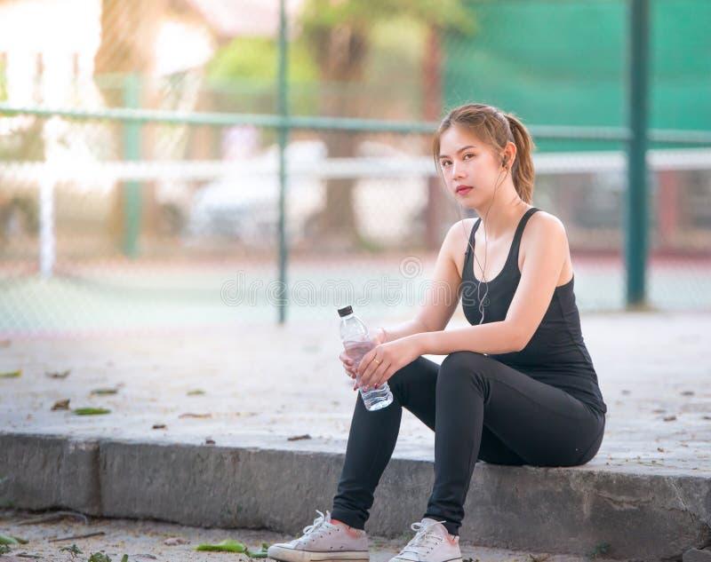 喝水的亚裔女孩健身妇女在跑步以后 库存图片
