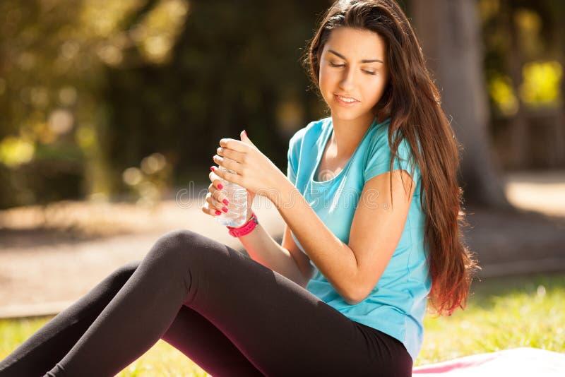喝水的年轻美丽的体育妇女 免版税图库摄影