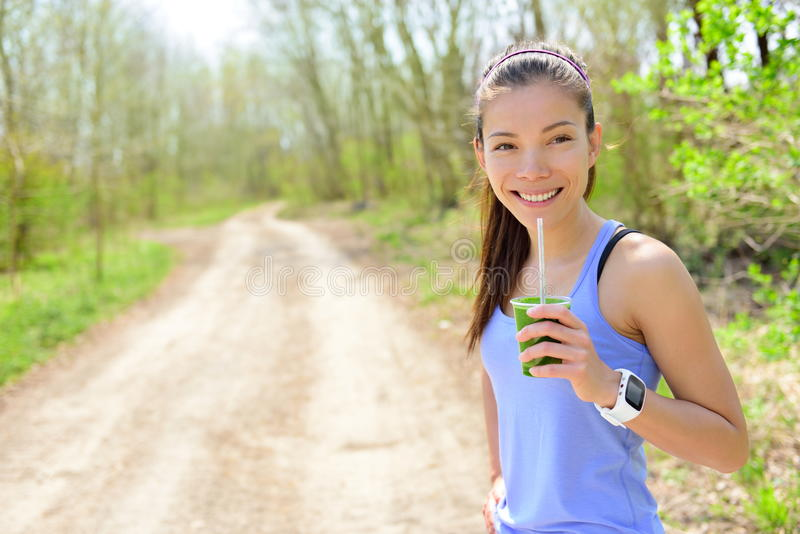 喝绿色圆滑的人佩带的smartwatch的妇女 库存照片