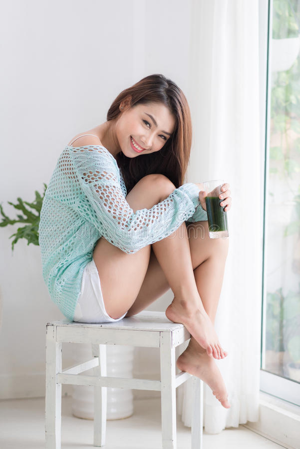 喝绿色新鲜蔬菜汁o的微笑的年轻亚裔妇女 图库摄影