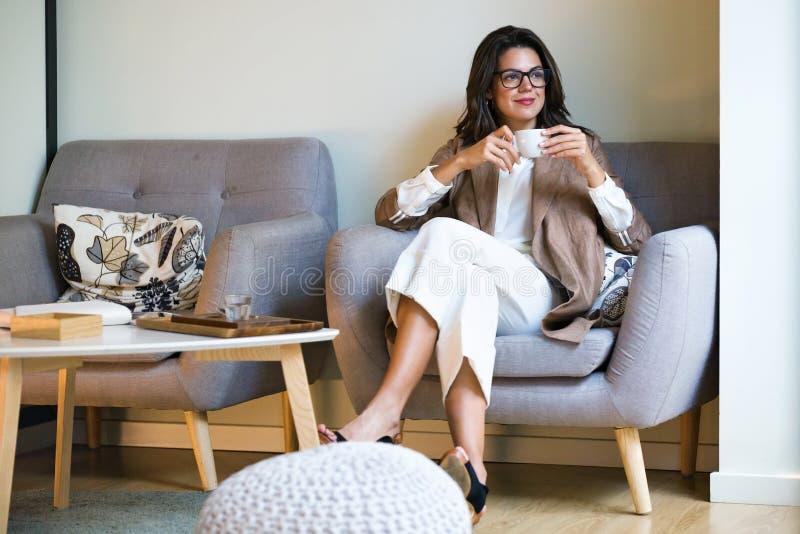 喝Matcha绿茶拿铁的可爱的年轻女实业家在咖啡馆 免版税库存图片