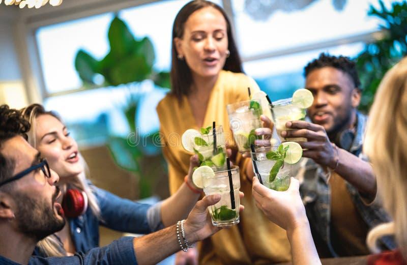 喝mojito在时尚鸡尾酒吧餐馆-与被喝乐趣的年轻人的友谊概念的最好的朋友 库存照片