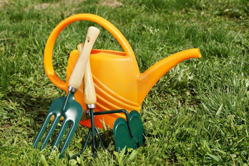 喷壶和园艺工具在草在庭院里 免版税图库摄影