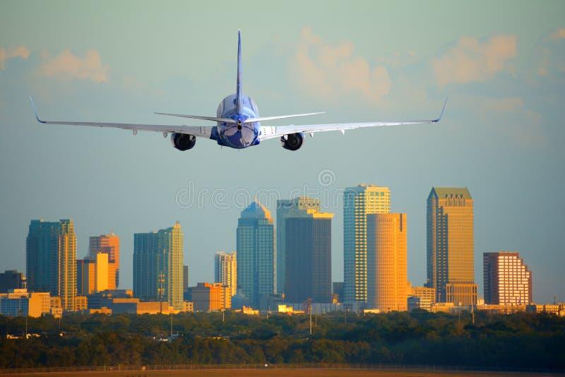 喷气式客机班机平面到达的或离去的坦帕国际机场在日落或日出的佛罗里达 免版税库存图片