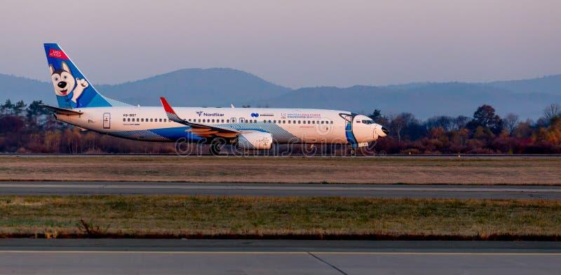 喷气式客机飞机NordStar航空公司波音737-800在跑道的 机体被绘当狗西伯利亚爱斯基摩人 图库摄影