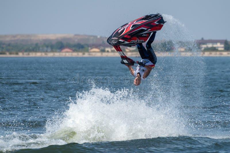 喷气机滑雪水体育的年轻人在获得的夏天在海滩的乐趣 免版税库存图片