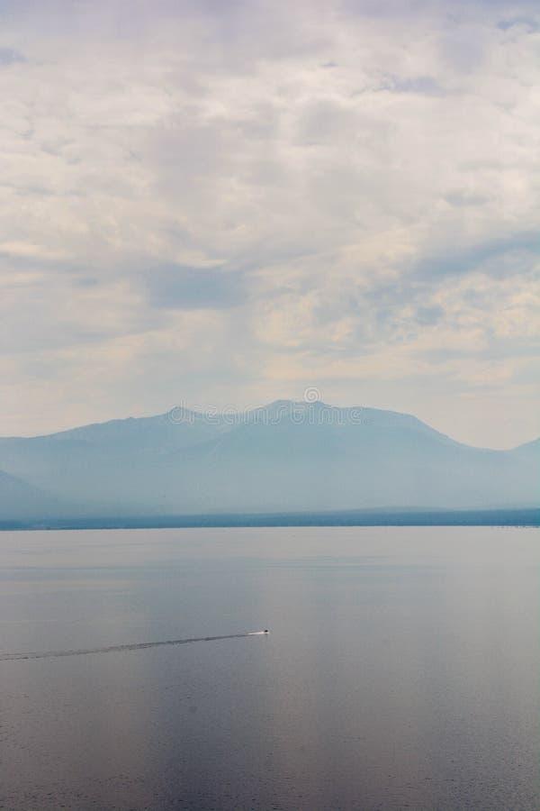 喷气机飕飕声横跨朦胧的烟的太浩湖的Skiier从野火 库存照片