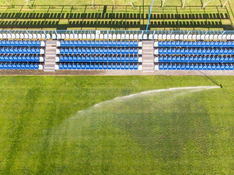 喷水隆头浇灌的橄榄球场 鸟瞰图 库存图片