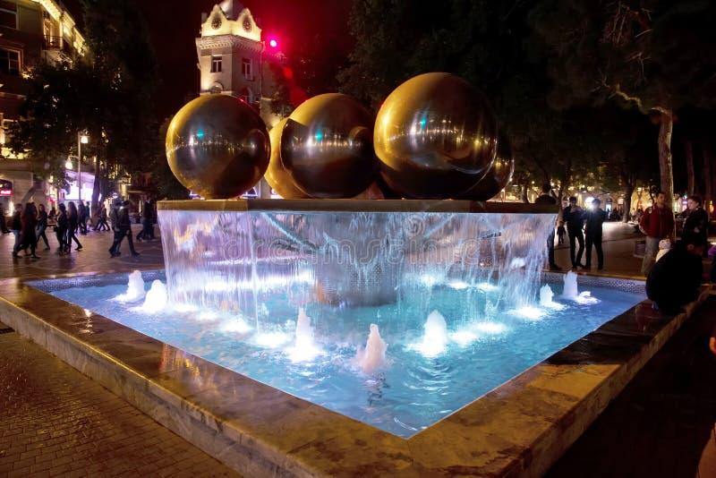 喷泉在市中心 对拥挤街道和人的看法在巴库阿塞拜疆 一个圆的公园喷泉的夜视 库存照片