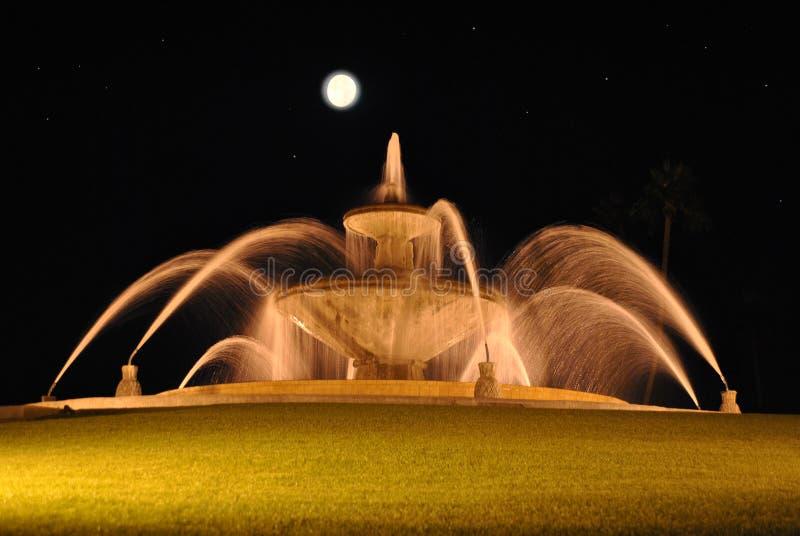 喷泉夜射击用被弄脏的水和满月和星 免版税库存照片