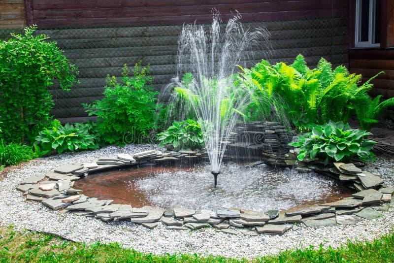 喷泉,石和绿草 库存照片