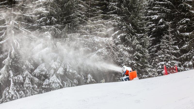 喷洒人为冰晶的雪枪滑雪滑雪道,snowmaking在冬季体育手段,树在背景中 库存图片