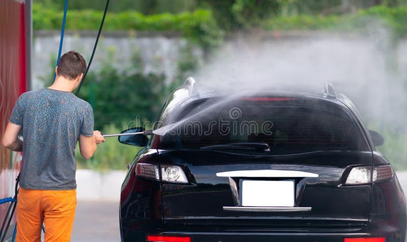 喷洒在他的汽车下的年轻人 图库摄影