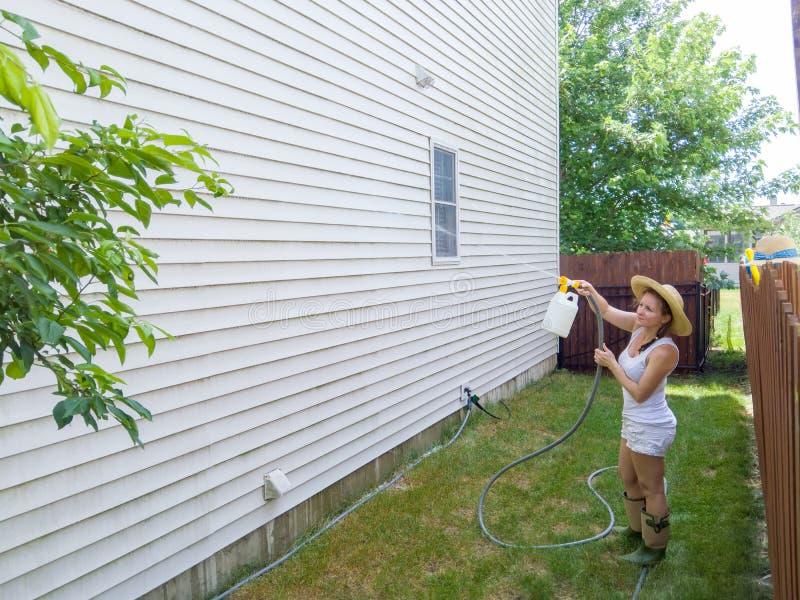 喷洒在房子房屋板壁下的可胜任的适合妇女 免版税库存图片