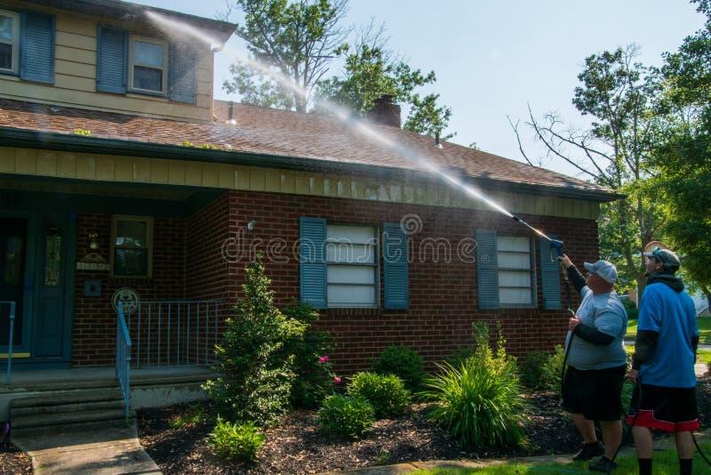 喷洒在房子的前面的两个年轻白种人人水解答作为他们的压力洗涤的服务一部分 免版税库存照片